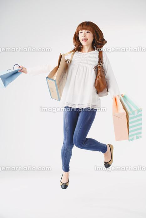 買い物袋を持ってジャンプする日本人女性の販売画像