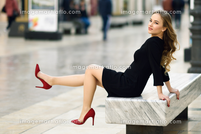 Funny blonde woman with beautiful legs in urban background. Beautiful young girl wearing black elegant dress and red high heels sitting on a bench in the street. Pretty russian female with long wavy hair hairstyle and blue eyes.