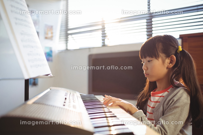 Concentrated girl practicing piano in class