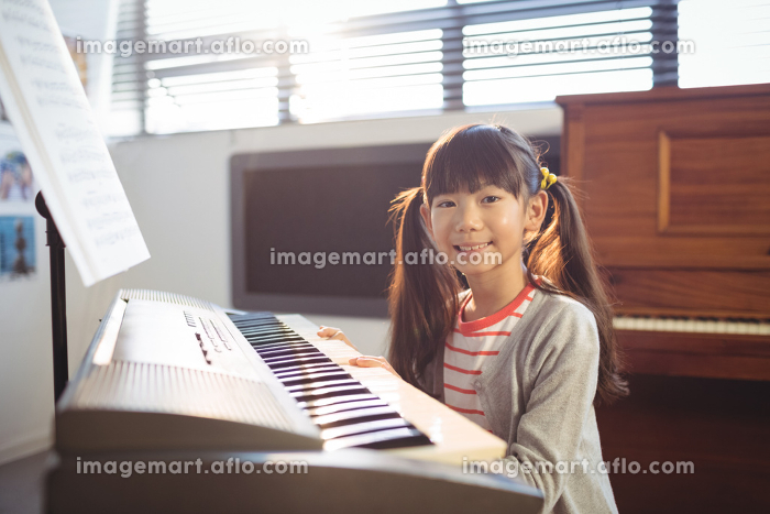 Portrait of smiling girl practicing pianoの販売画像
