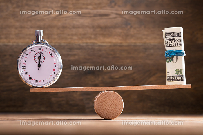 Close-up Of Stopwatch And Rolled Up Banknotes On Seesawの販売画像