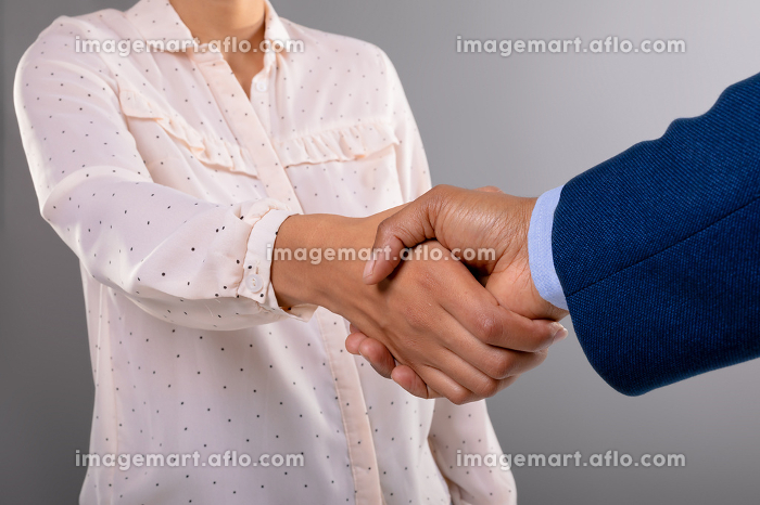 Mid section of businessman and businesswoman shaking hands against grey background. business agreement and professionalism conceptの販売画像