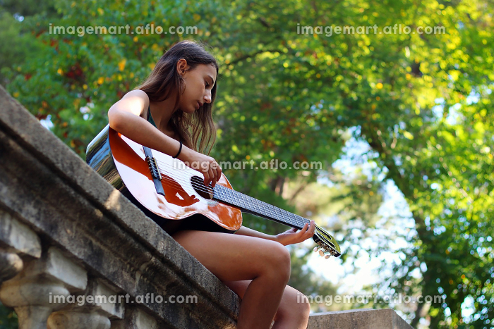 Music Concept: Young and Beautiful woman playing Spanish guitar.の販売画像