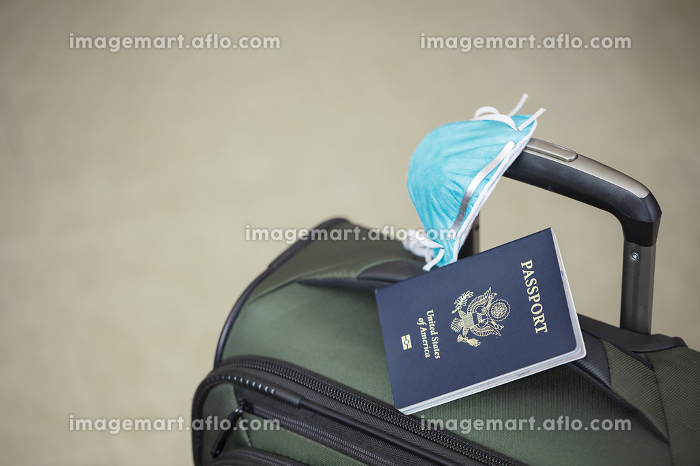 personal luggage with passport and flu virus mask to protect against coronavirus, global epidemic conceptの販売画像