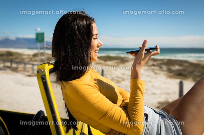 Caucasian woman lying on a beach buggy by the sea talking on smartphone. beach break on summer holiday road trip.の販売画像
