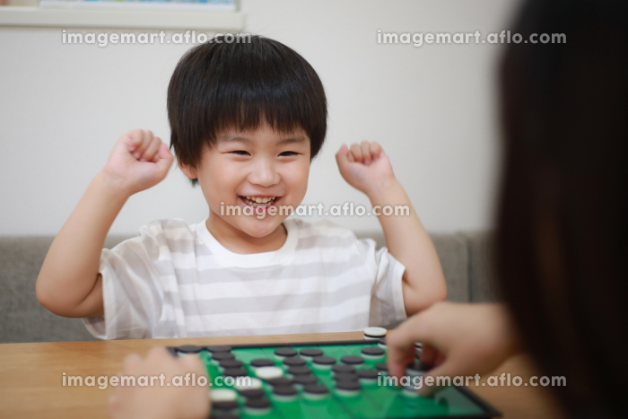 オセロで勝ち喜ぶ男の子の販売画像