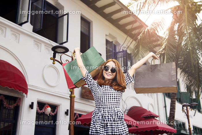 Happy asian girl in sunglasses holding shopping bags