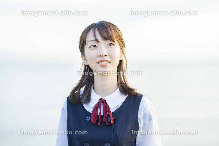 海を背景に、笑顔を見せる女子高生の販売画像