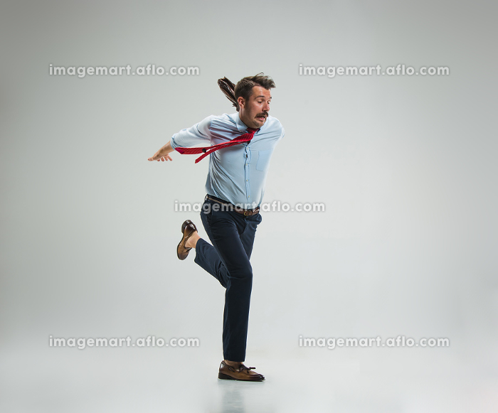 Businessman running with a briefcase, isolated on gray backgroundの販売画像