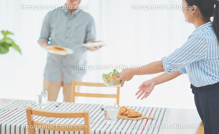 出来た料理を運ぶ男性の販売画像