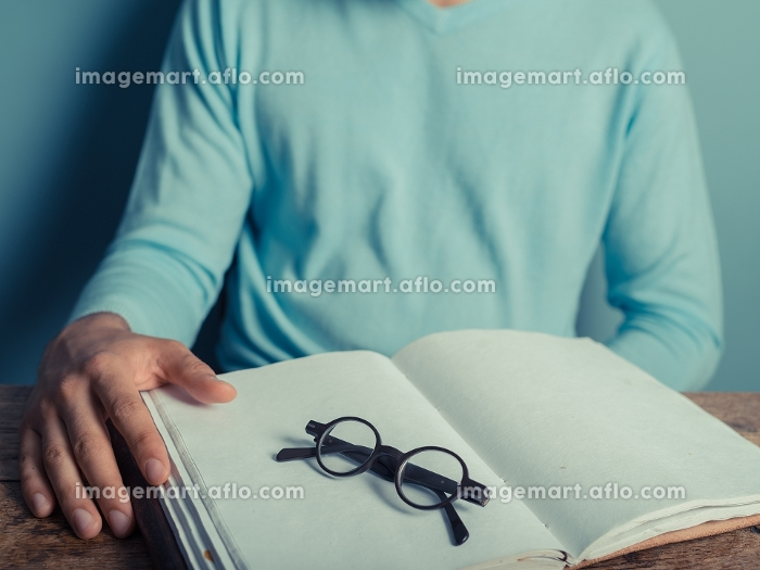 A young man is sitting at a table with a big notepad and a pair of glasses in front of himの販売画像
