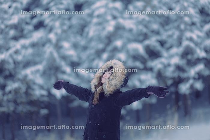 雪が積もった森で手を広げて立つ日本人女性