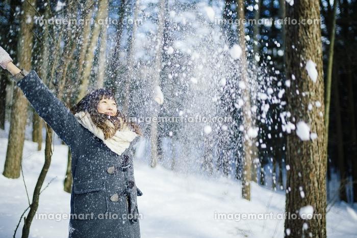 雪を上に投げる日本人女性の販売画像