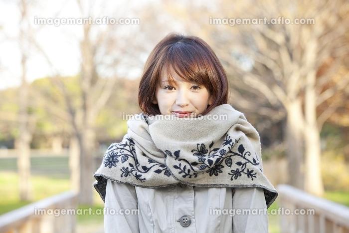 マフラーを巻いて微笑む女性の販売画像