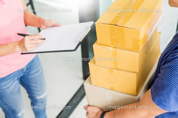 woman courier holding a parcel Shipping Mail appending signature signing delivery note after receiving package from delivery man.の販売画像