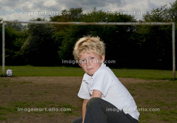 Schoolboy in front of football goalpostの販売画像