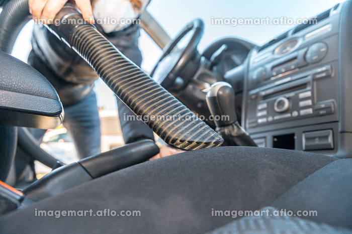 vacuuming the interior of a passenger car using an industrial vacuum cleaner. man works in protective medical mask. protection against coronavirusの販売画像