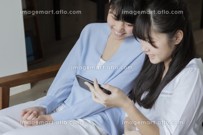スマートフォンを見る女の子の販売画像