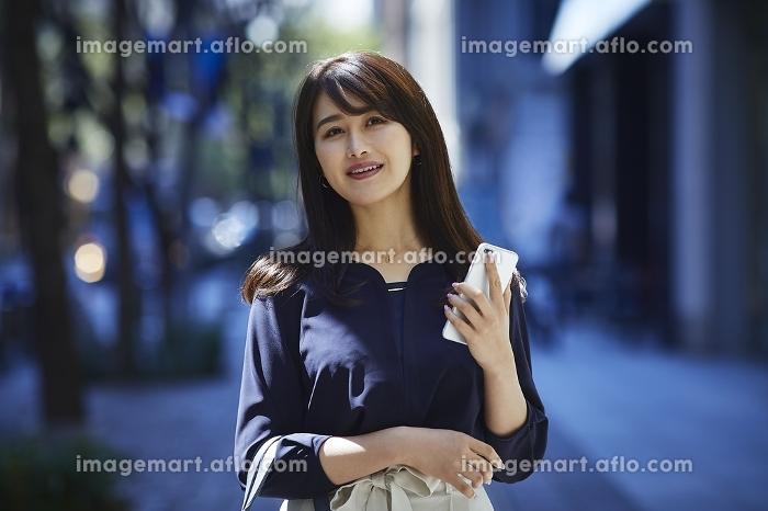 携帯電話を片手に街を歩く日本人女性のポートレートの販売画像