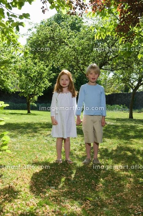 Children holding hands in backyardの販売画像
