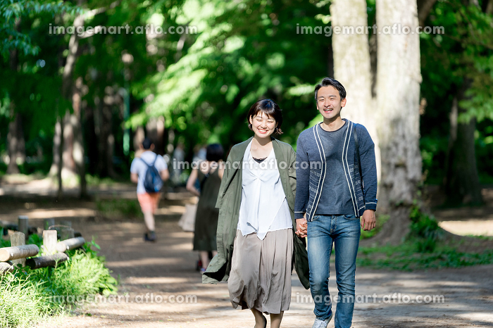 新緑の爽やかな小道を散歩するカップル(デート・夫婦)の販売画像