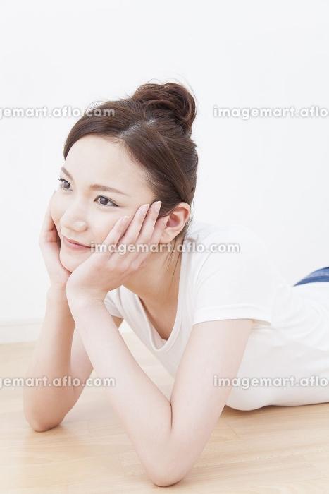 頬杖をついて寝転ぶ女性の販売画像