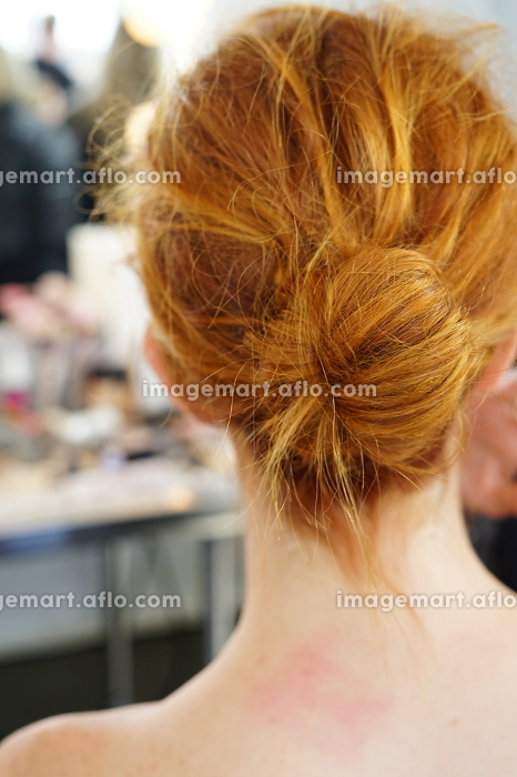 Young woman sitting for hair and makeup with a messy bun hairstyleの販売画像