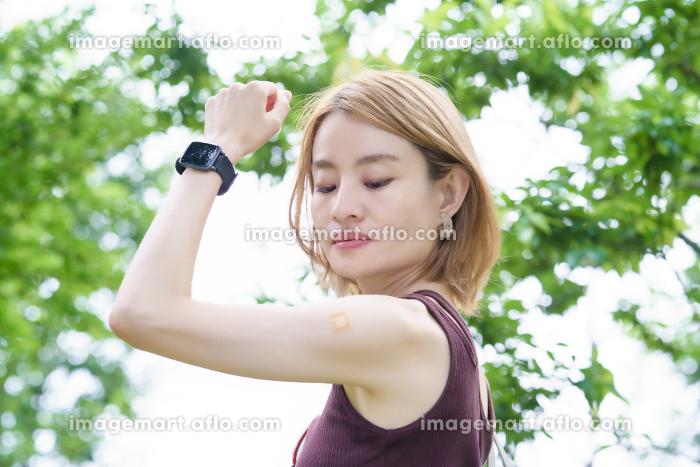 ワクチン接種を終えて、パッチが貼られた女性の腕の販売画像