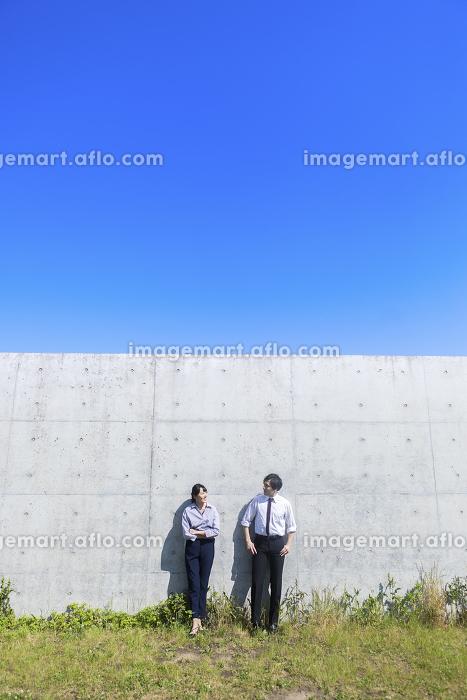 コンクリートの壁の前に立つ男女の販売画像