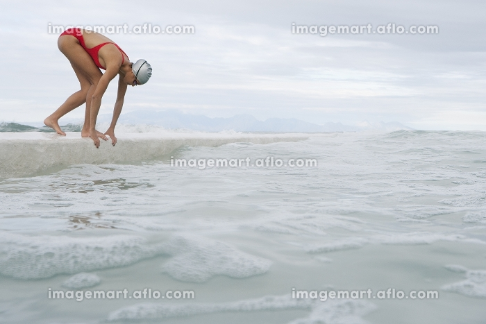 Runner jumping into water from dockの販売画像