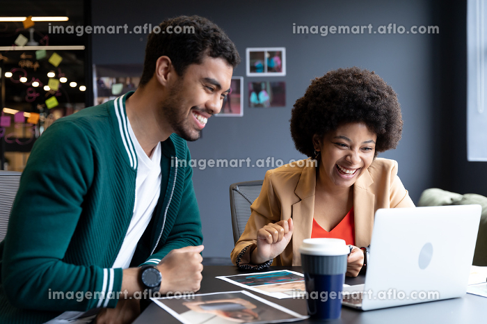Happy diverse businessman and businesswoman using laptop in creative office. technology in business office workplace during covid 19 coronavirus pandemic.の販売画像