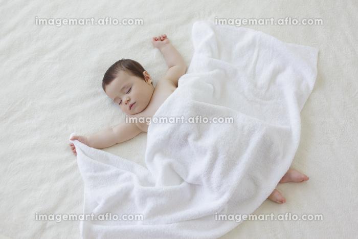 タオルを握って眠る赤ちゃんの販売画像