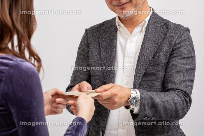 娘にお小遣いをあげている父の販売画像