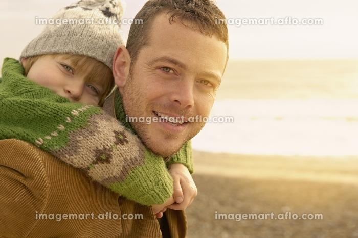 ビーチで父親におんぶされる子供の販売画像