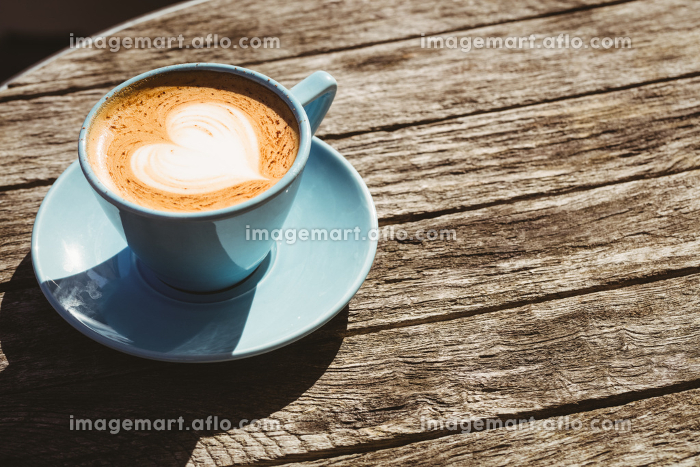 Cup of cappuccino with coffee art on wooden tableの販売画像