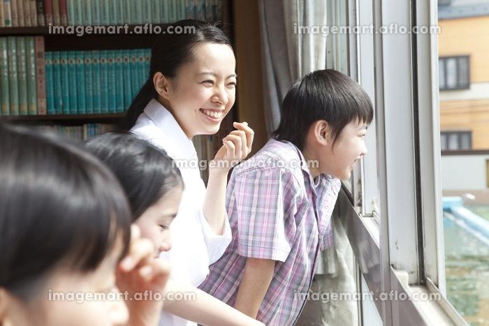 図書室の窓から外を見る小学生と女教師の販売画像