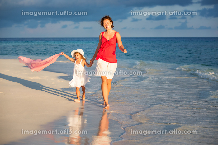 Mother and daughter walking on the beachの販売画像