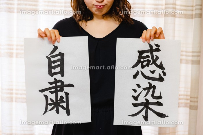 筆で書いた自粛と感染の文字を持つ女性 比べる 考えるの販売画像
