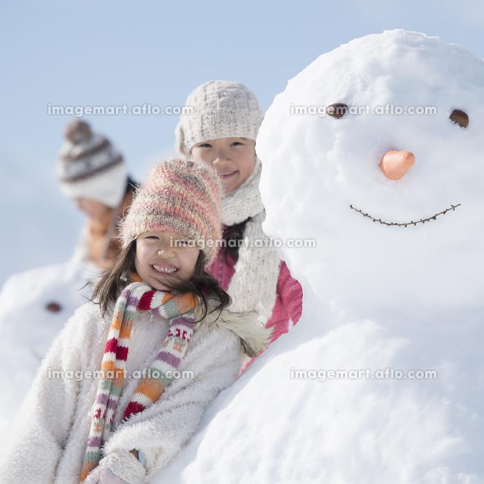 雪だるまの周りで微笑む小学生の販売画像