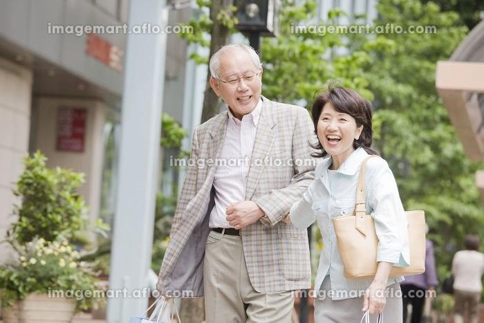 街中を腕を組みながら歩く老夫婦の販売画像