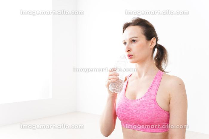 スポーツウェアを着て水分補給をする外国人の女性の販売画像