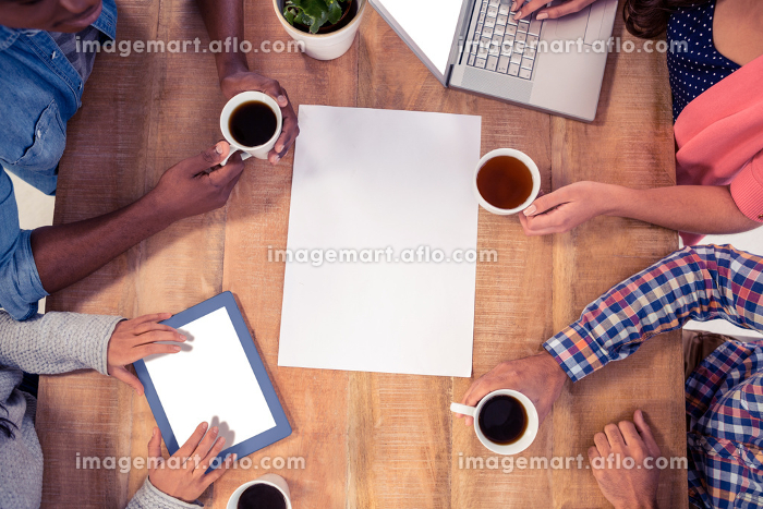 Professionals using technologies while holding coffee cupsの販売画像