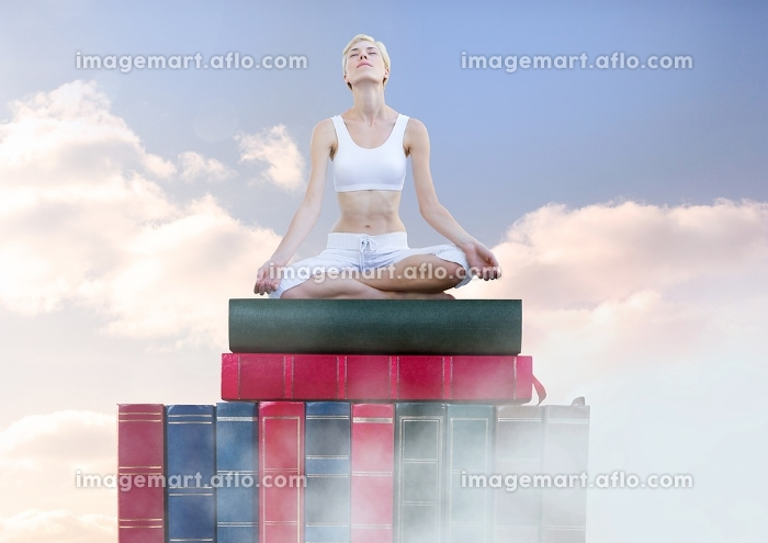 Woman meditating relaxing on Books stacked by skyの販売画像