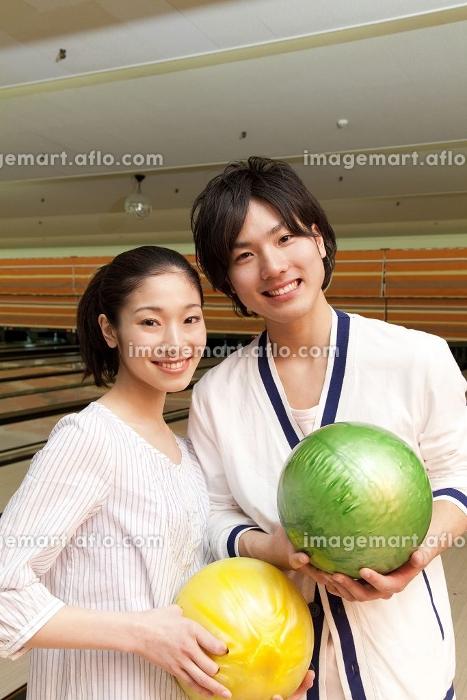 ボウリング球を持って微笑む男女の販売画像