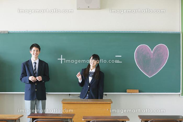 黒板に描いたハートと高校生カップル