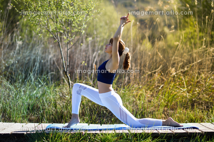 Young woman doing yoga in nature. Female wearing sport clothes.の販売画像
