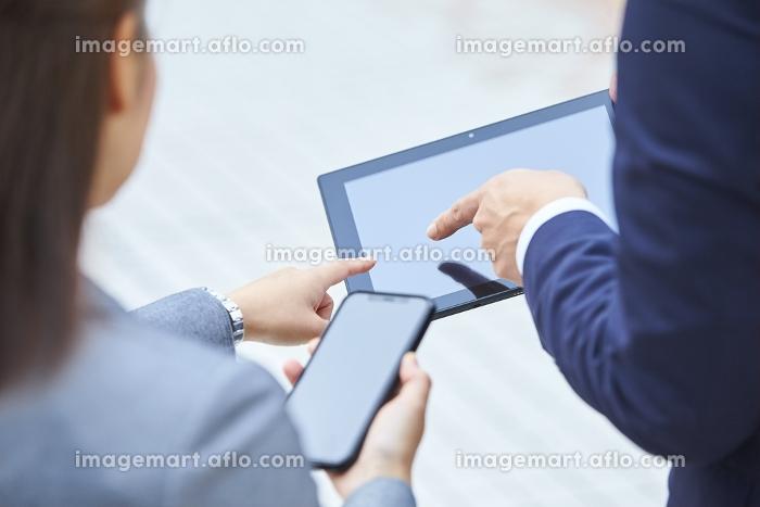 スマートフォンとタブレットを指さすビジネスマンとビジネスウーマン