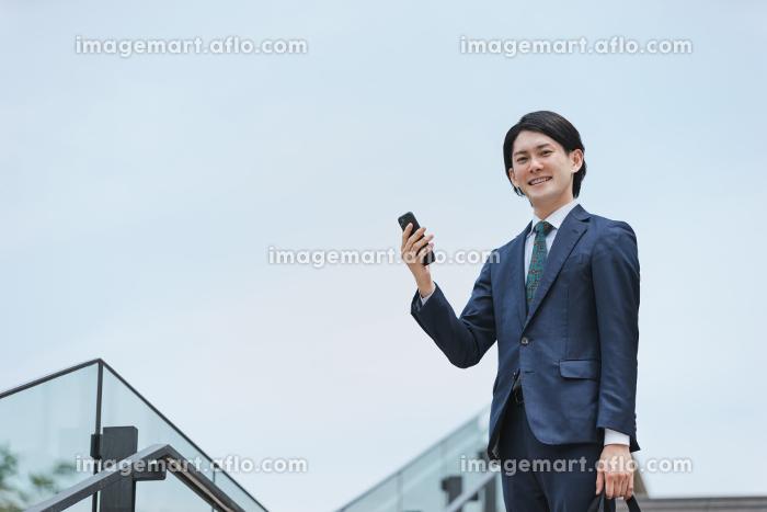 IoTのイメージ 通勤先から家の家電を操作する男性の販売画像