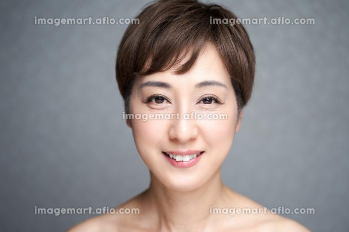 カメラ目線でほほ笑む中年の日本人女性の販売画像