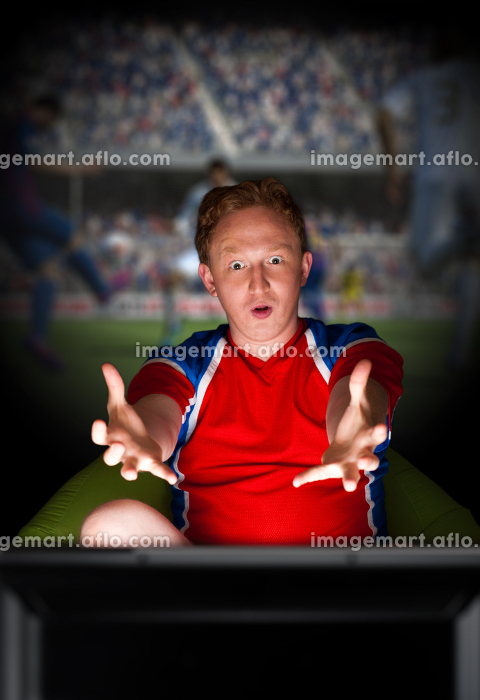 Closeup portrait of young man wearing sportswear fan of football team is watching tv and rooting for his favorite team. Sitting on beanbag alone at night. Light from television.の販売画像